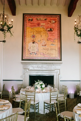 Round reception table with low centerpiece in front of fireplace and large map at bel air bay club