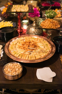 Engagement party table with Moroccan food in metallic platters, glass stands
