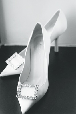 White Kate Spade pointed-toe pumps with a rhinestone square buckle