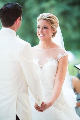 Bride in illusion neckline romona keveza ball gown wedding dress holding groom's hand white tuxedo