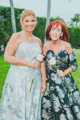 mother of the bride and groom in complementary black, white, and silver floral gowns
