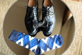 black dress shoes for groom, black bow tie, blue argyle socks