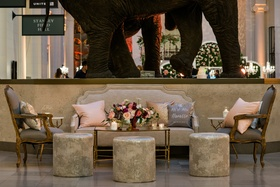 Lounge area by elephant sculpture at The Field Museum grey armchair french style settee and ottoman