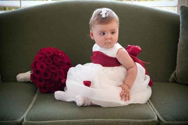 Baby flower girl with big red bow on white dress