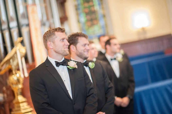 Brian Leonard, running back, in a black tuxedo with peach rose boutonniere at his wedding ceremony