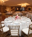 Wedding reception tables with white tablecloths and pink centerpieces