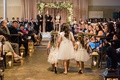three flower girls in white dressed walk down aisle jewish wedding