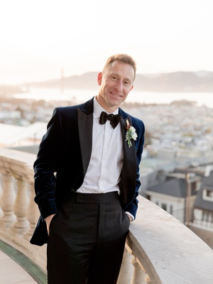 groom on balcony in navy velvet jacket, black lapels, black trousers, bow tie