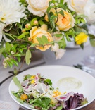 wedding reception wood table clear charger plate white salad plate fresh greenery radish tomato