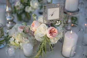 Wedding reception table with table number in a silver vine frame atop white roses, hydrangeas