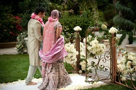 Indian groom and bride walk barefoot outside