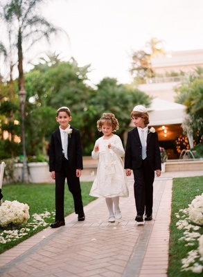 Flower girl in a long sleeve dress with bridal party boy attendants in black tuxedos and grey ties