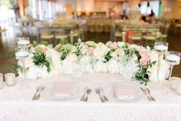 sweetheart table with textured linen, garland of flowers and greenery