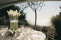 round tables with large centerpiece overlooking ocean