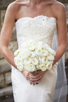 Bride in strapless Elizabeth Fillmore wedding dress holding all white bouquet of ranunculuses