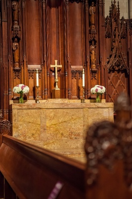 Marble cathedral altar with cross and short floral arrangements