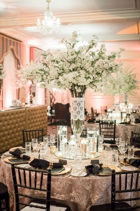 Wedding reception round table texture linen black chairs candles white flowers chandeliers round