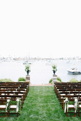 Wood ceremony chairs with green garlands on lawn in front of San Diego bay