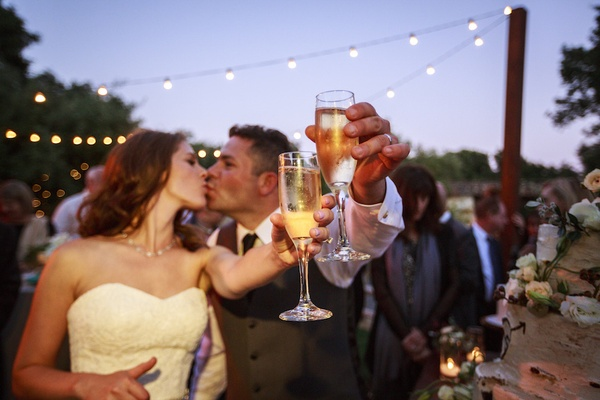Bride and groom kiss and raise glasses of Champagne at outdoor wedding reception