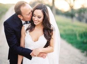 Groom kisses bride on cheek at outdoor wedding