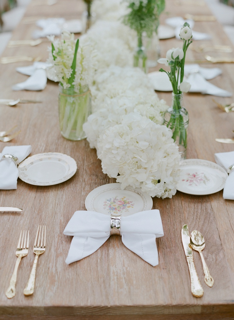 Wood reception table with floral china and napkin in bow shape