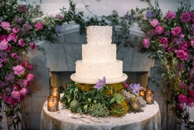 lace patterned three-tier cake on a table with succulents