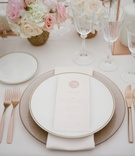 Wedding reception with charger plate napkin china and menu card with wax seal and rose gold fork