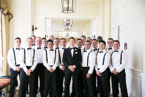 Groom in tuxedo with groomsmen in black pants white shirts black bow ties and suspenders