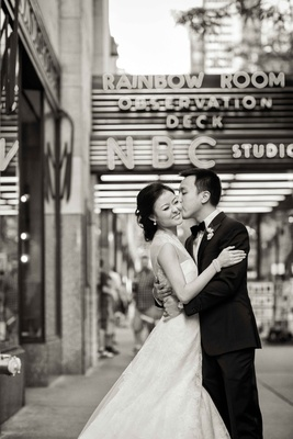 Black and white photo of Chinese American bride and groom in front of Rainbow Room wedding venue NYC