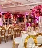 Wedding reception all white ballroom with candles candelabra pink fuchsia flower centerpieces
