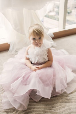 Little blonde flower girl sitting on carpet with white fabric floret bodice and layered pink skirt