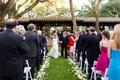 Newlyweds walking up petal-lined grass aisle