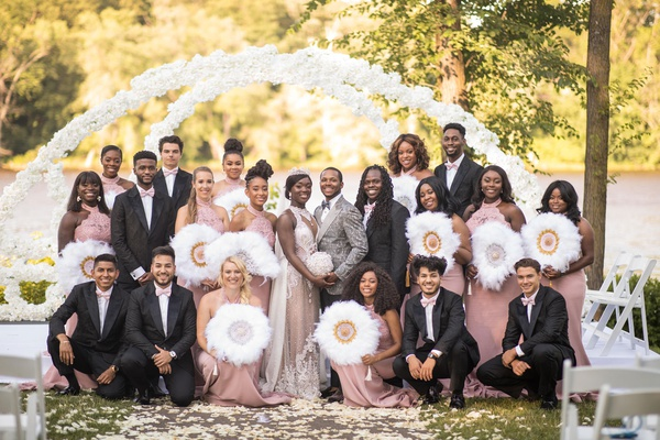 bride and groom with groomsmen pink ties and bridesmaids dresses gold silver white feather fans