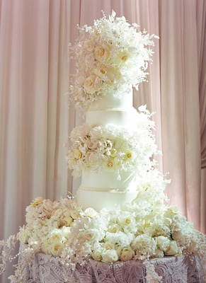 Wedding cake with fresh flowers and sugar flowers decorating base and tiers layers wedding reception