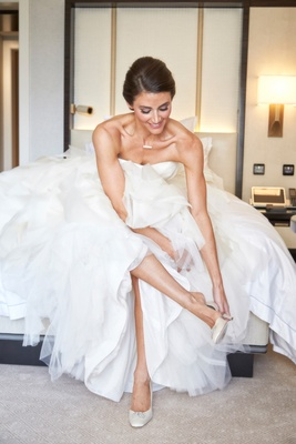 a bride in a wedding dress featuring a tulle skirt puts on white high heel shoes while getting ready