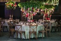wedding reception table with vineyard chairs, inverted floral arrangement with greenery