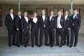 Groom and groomsmen in black tuxedos and white vests, bow ties