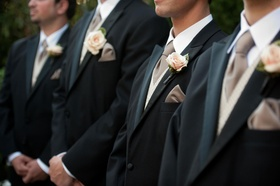 Groomsmen in tuxedos with mauve ties and pink roses