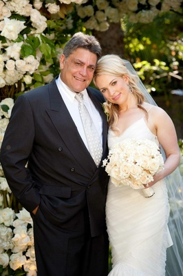 Bride smiles with father of bride in front of roses