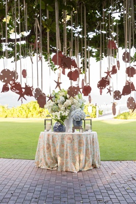 Cocktail hour decor table with seashell starfish shaped escort cards hanging from tree by ocean