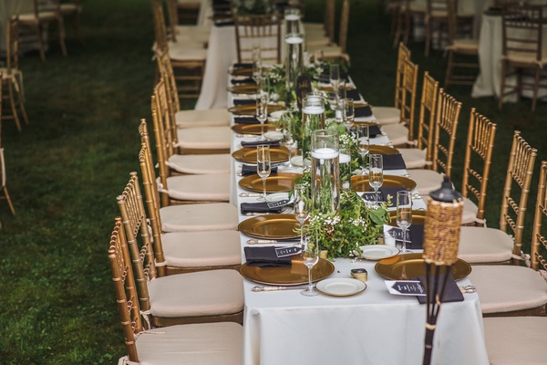 long reception table, white linens, gold chiavari chairs, gold chargers