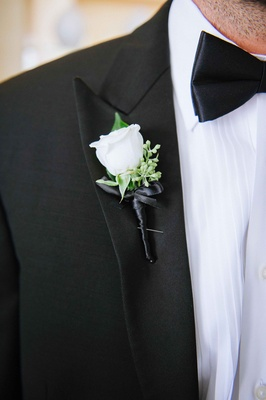 Groom in black tuxedo, bow tie, ivory rose boutonniere on right lapel