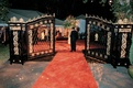 Wedding reception with a black and gold iron gate and red carpet