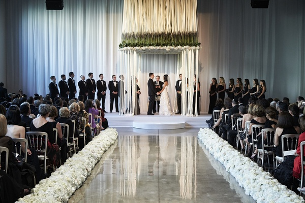 modern jewish indoor ceremony with suspended flowers and ribbons forming chuppahs