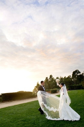 Groom and bride at sunset with flower trim veil
