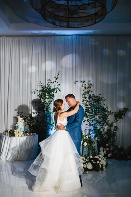 wedding reception first dance drapery wall greenery climbing up flowers on dance floor sweetheart