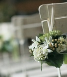 Wedding ceremony seats decorated with bundles of green and white flowers