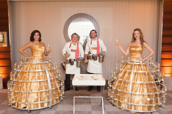 Servers in gold ball gowns with metal champagne holders on skirts and oyster shucker servers