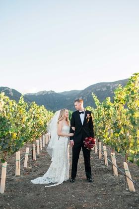 bride in jim hjelm wedding dress and groom stand in vineyard vines california red bouquet of flowers