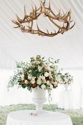 White tent with flower arrangement green leaves white flowers antler chandelier overhead